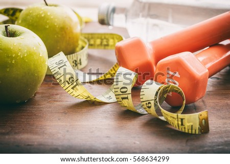 Green apples, dumbbells and measuring tape on wooden background