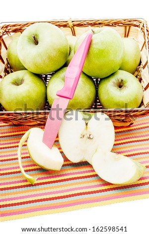 Green apples in a basket and with knife - stock photo