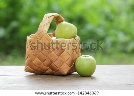 green apples in a birchbark basket, on wooden table - stock photo