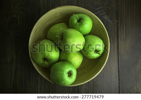 Green apples in bowl on wooden table, top view - stock photo