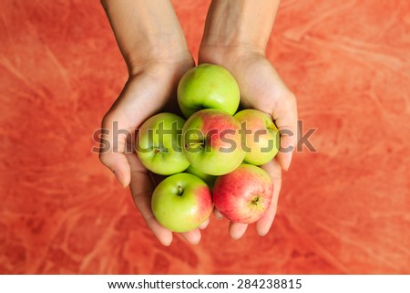 Green apples in woman's hands on red background