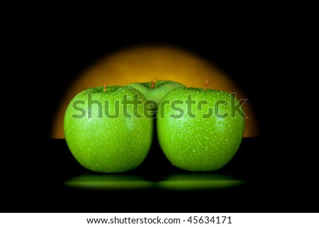 green apples in yellow light isolated on black - stock photo
