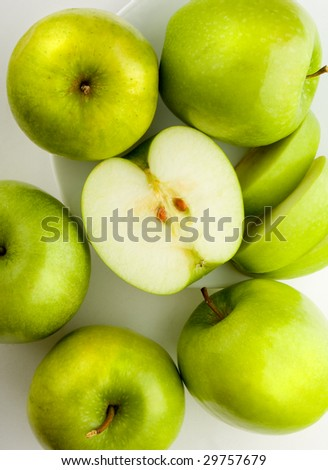 Green apples on a white plate - stock photo