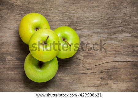 Green apples on a wooden background. Top view. - stock photo