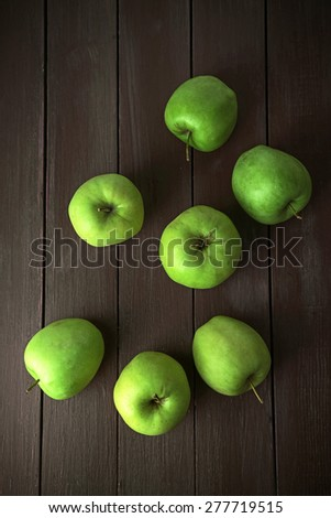 Green apples on wooden table, top view - stock photo
