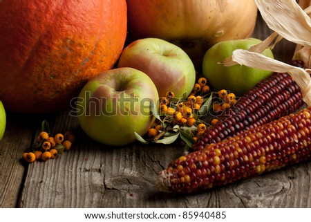 Green apples, orange berries and corns on old wooden table