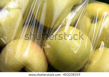 Green apples packed under plastic film