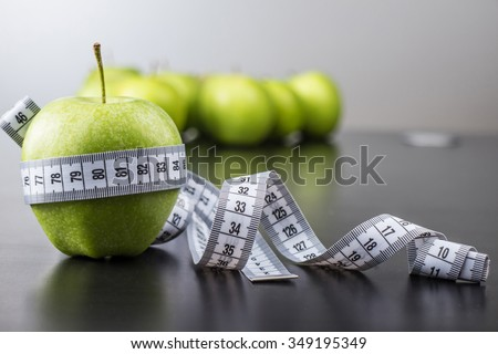green apples with measuring tape - stock photo