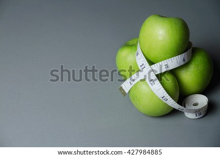 green apples with measuring tape on Grey background - stock photo