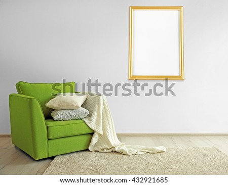 Green armchair and picture frame on light wall background - stock photo