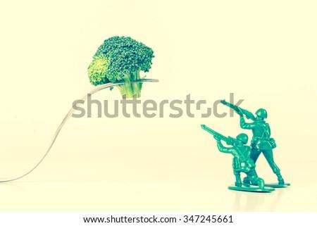 Green army men attack a threatening kitchen fork - stock photo