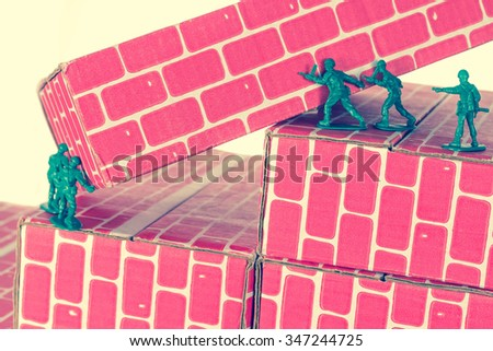 Green army men using teamwork to make progress up the toy brick stairs - stock photo