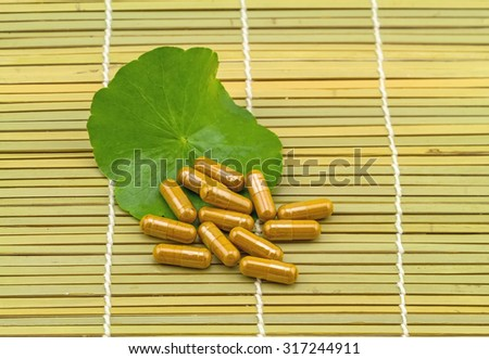 Green Asiatic Pennywort (Centella asiatica ) and yellow pill capsules on brown bamboo weave background - stock photo