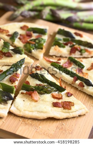 Green asparagus and bacon tarte flambee or Flammkuchen, a typical Alsatian and South German dish, photographed on wooden board with natural light (Selective Focus, Focus one third into the image) - stock photo