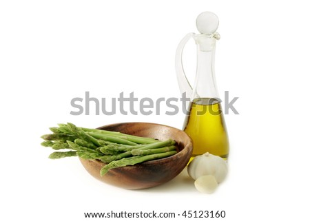 Green asparagus in bowl and jug with olive oil. Isolated on white background.