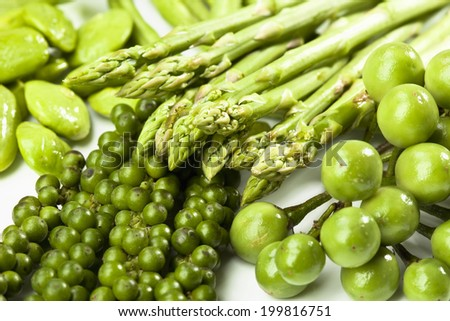 Green asparagus, Sator beans, peppercorns and eggplants, close up - stock photo