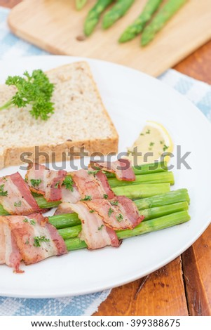 Green asparagus with bread and butter on a white plate.
