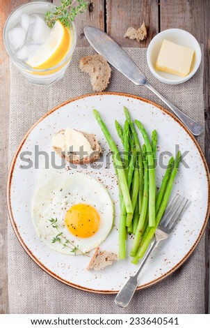Green asparagus with fried egg and bread with butter on a white plate. Top view. - stock photo