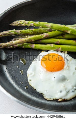 Green asparagus with fried egg on the frying pan - stock photo