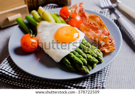 Green asparagus with fried eggs, bacon and tomatoes. Selective focus. - stock photo