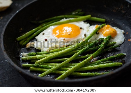 Green asparagus with fried sunny side up egg on black background. Close up, selective focus. Healthy breakfast food - stock photo