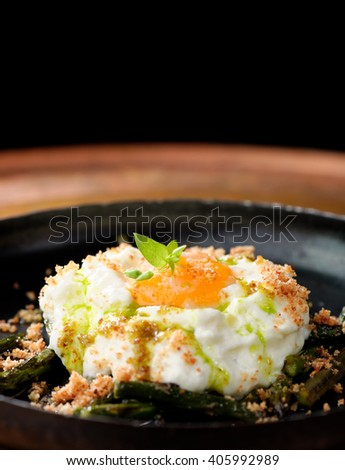 Green asparagus with poached egg in a frying pan - stock photo