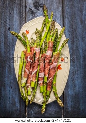 Green asparagus wrapped in ham in plate on  rustic blue wooden background, top view - stock photo
