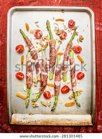 Green Asparagus wrapped in ham  with tomatoes, parmesan, Walnut  and dried apricot in old backing tray on red wooden background, top view - stock photo