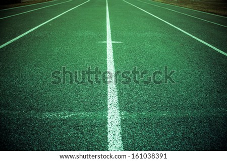 Green athletic field running track with lines