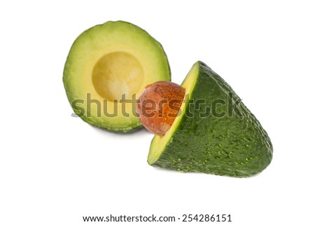 Green avocado cut in half with a bone isolated on white - stock photo
