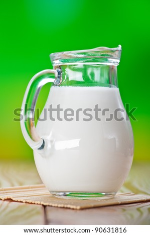 green background, Close-up, glass decanter of milk is on bamboo napkin on wooden table