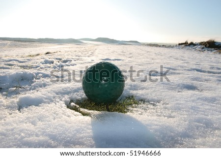 green ball on a snow covered links golf course in ireland in winter - stock photo