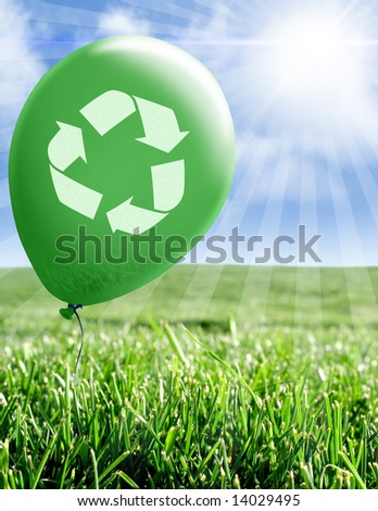 Green balloon with recycle symbol over field of grass - stock photo