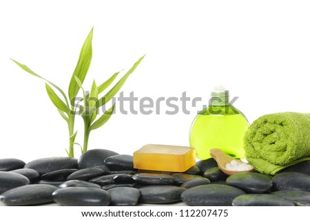 green bamboo sprout with massage oil and towel ,soap on pebbles