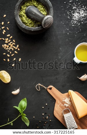 Green basil pesto - italian recipe ingredients on black chalkboard from above. Parmesan cheese, basil leaves, pine nuts, olive oil, garlic, salt, pepper and mortar. Layout with free text space. - stock photo