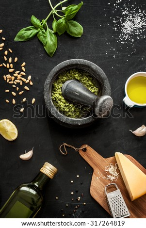 Green basil pesto - italian recipe ingredients on black chalkboard from above. Parmesan cheese, basil leaves, pine nuts, olive oil, garlic, salt, pepper and mortar. - stock photo