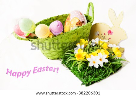Green basket with colored eggs, flowers and decorations.