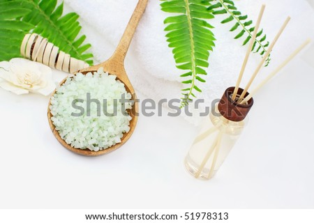 Green bath salts in a wooden spoon with essential oils and white towel. Extreme shallow DOF with selective focus on bath salts. Room for your text. - stock photo