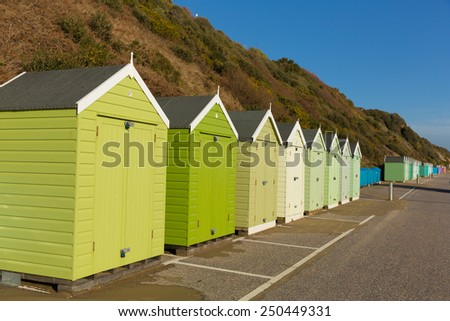 Green beach huts in a row with blue sky traditional English structure and shelter found at the seaside - stock photo
