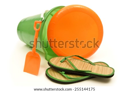 Green Beach Pail With Flip Flops And Orange Disc/ Time For Summer Fun - stock photo