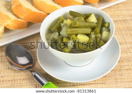 Green bean and potato hotpot in white bowl with a spoon beside and baguette slices in the back (Selective Focus, Focus on the first half of the hotpot)