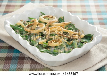 Green bean casserole - a traditional Thanksgiving side dish. Green beans mixed with cream of mushroom soup and topped with french-fried onions. - stock photo