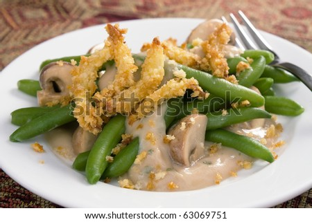 Green bean casserole - a traditional Thanksgiving side dish. Green beans with cream of mushroom soup and topped with french-fried onions. - stock photo