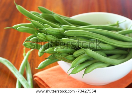 Green beans in a white bowl on orange napkin - stock photo