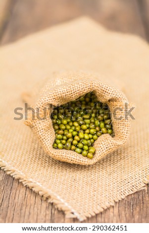 green beans in sack bags with sack cloth on old wooden background - stock photo