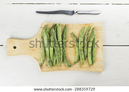 Green beans on cutting board with knife on white wooden table - stock photo