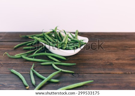 Green beans on wooden background in rustic style - stock photo