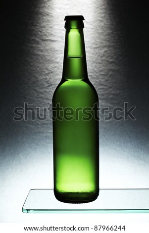 Green beer bottle in front of stone tile - stock photo