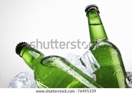 Green beer bottles on ice over white background - stock photo