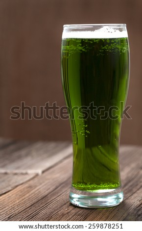 Green beer in glass with bubbles for st. patricks day on vintage wooden background - stock photo